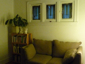 talman green couch with bookshelf and stained glass windows